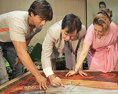 Shahrukh and Saira Bano help Dilip Kumar as he signs the poster.