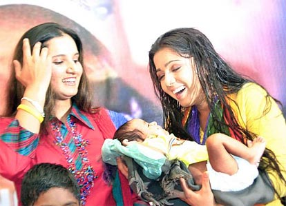 Sania Mirza and Telgu actress Charmee applaud a baby during the launch of 'save a child '