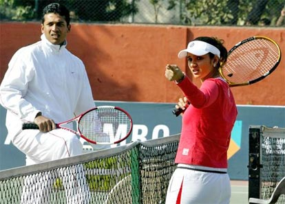 Sania Mirza talks with Mahesh Bhupathi during a coaching clinic for children